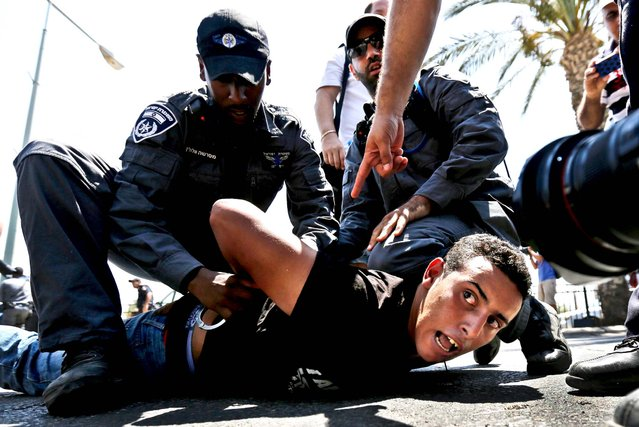 Police detain a protester during a demonstration in the southern Israeli city of Beersheba, on July 15, 2013. Protesters scuffled with Israeli police during a demonstration against an Israeli cabinet plan to relocate some 30,000 Bedouin citizens from  southern Negev. According to an Israeli police spokesman, 800 protesters gathered for the demonstration of which 15 were detained. (Photo by Amir Cohen/Reuters)