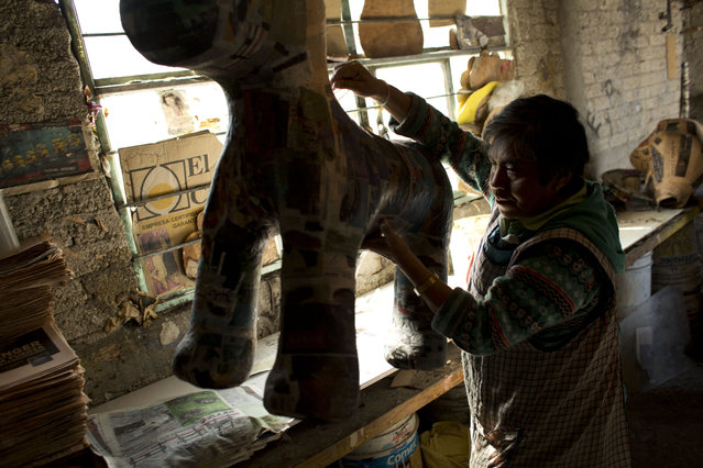 "In this January 20, 2015 photo, Cecilia Albarran Gonzalez, 54, lifts a freshly papier-mached piñata in the form of My Little Pony, to carry it outside to dry, at her family's home workshop in the Iztapalapa neighborhood of Mexico City. Competition from craftsmen using lower quality materials and techniques has cut their sales in half. But Albarran said some people still choose to buy their higher priced ""artistic"" piñatas. (Photo by Rebecca Blackwell/AP Photo)"