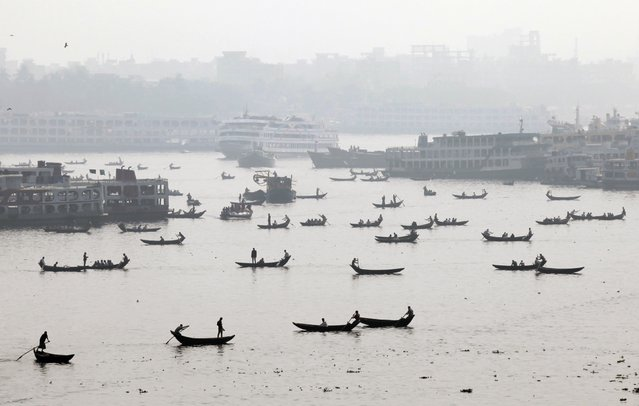 Bangladeshis on country boats cross the Buriganga River in Dhaka, Bangladesh, Thursday, January 29, 2015. (Photo by A. M. Ahad/AP Photo)