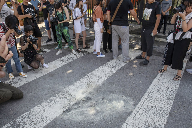 People take photographs and record video footage of white markings on the ground outside the U.S. Embassy following an explosion in Beijing, China, on Thursday, July 26, 2018. (Photo by Gilles Sabrie/Bloomberg via Getty Images)