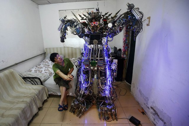 "Chinese inventor Tao Xiangli controls a robot with a remote controller in Beijing, on August 9, 2013. The self-taught inventor built the home-made robot, named ""The King of Innovation"", out of scrap metal and electronic wires that he bought from a second-hand market. (Photo by Kim Kyung-Hoon/Reuters)"
