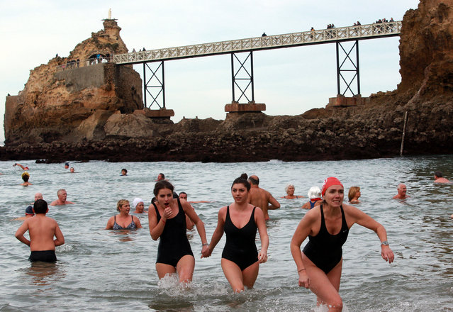Enthusiasts from the long-established swimming club Les Ours Blancs (The Polar Bears), paddle during an annual swim in Biarritz, southwestern France, with the Virgin Rock in the background, Sunday, December 27, 2015. Most people were dressed in red, white and blue colors following the latest attacks in France. (Photo by Bob Edme/AP Photo)
