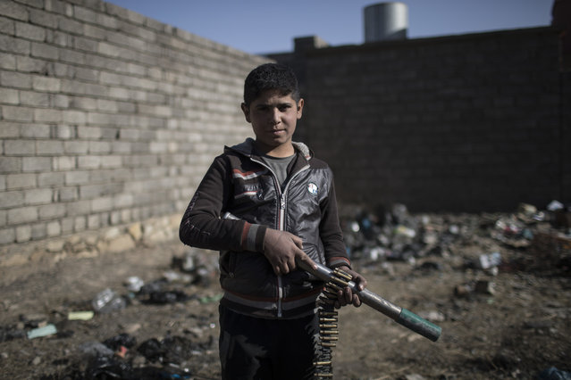 A boy poses for a photo as he plays with a homemade toy gun in Qayara, south of Mosul, Iraq, Tuesday, November 22, 2016. (Photo by Felipe Dana/AP Photo)