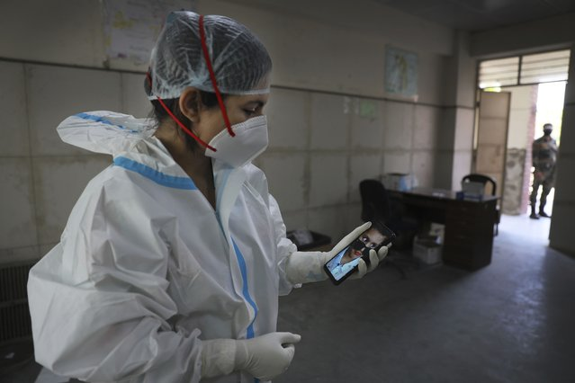 "Health worker Kavita Sherawat, 30, shows a photograph of her son Parakhshit before proceeding to take samples to test for COVID-19, in New Delhi, India, Thursday, March 18, 2021. Despite dutifully wearing masks and always washing her hands, Sherawat got infected, as did her husband, parents and in-laws. While doctors and nurses were cheered as heroes during the lockdown, people avoided her, fearing infection. She tested thousands of sick and gasping people as they arrived at hospitals, not knowing if the gear she wore was adequately protecting her. ""That fear changes you as a person. You start valuing your life more"", she said. (Photo by Manish Swarup/AP Photo)"