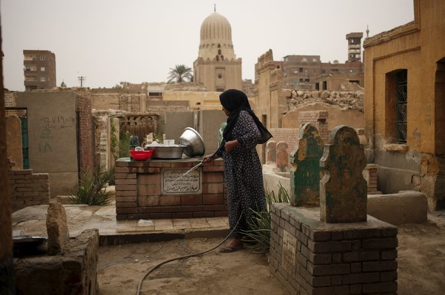 A woman who lives in the Cairo Necropolis cleans a tomb, outside her home in Cairo, Egypt, October 23, 2015. In the sprawling Cairo Necropolis, known as the City of the Dead, life and death are side by side. Amid a housing crisis in Egypt, and with the population of greater Cairo estimated at about 20 million, people count themselves lucky to have a place to call home in the graveyards that date back hundreds of years. (Photo by Asmaa Waguih/Reuters)