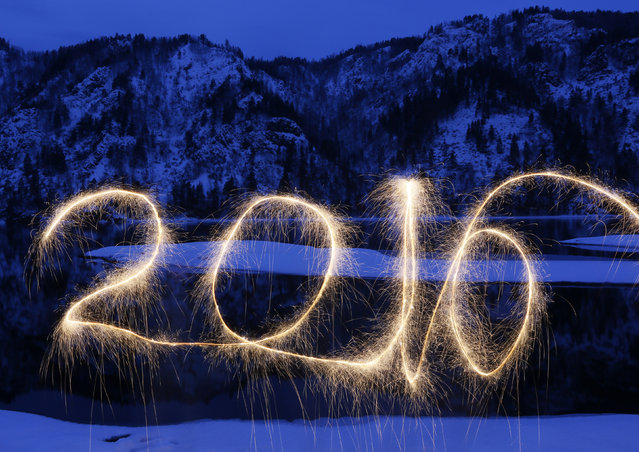 """The numbers """"2016"""" are written in the air with a sparkler on a bank of the Yenisei River in the Taiga district, near the town of Divnogorsk outside Krasnoyarsk, Siberia, Russia, December 31, 2015. (Photo by Ilya Naymushin/Reuters)"""