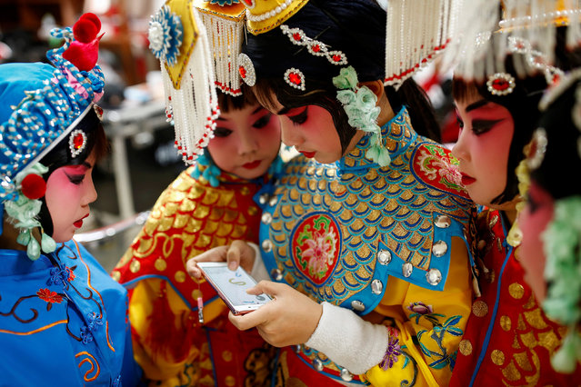 A participant plays a game on her phone as others watch during a break in a traditional Chinese opera competition at the National Academy of Chinese Theatre Arts in Beijing, China, November 26, 2016. (Photo by Thomas Peter/Reuters)