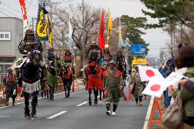 Horsemen, wearing medieval samurai armours from Soma Nomaoi Festival, attend the opening of a ceremony welcoming before the arrival of the torch bearer at Hibarigahara Festival Site, during the last leg of the first day of the Tokyo 2020 Olympic torch relay, in Minamisoma, Fukushima prefecture, Japan, March 25, 2021. (Photo by Issei Kato/Reuters)