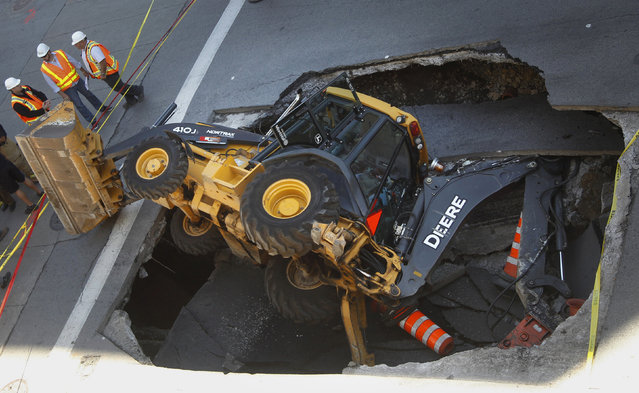 A construction vehicle lies where it was swallowed by a sinkhole on Saint-Catherine Street in downtown Montreal, August 5, 2013. (Photo by Christinne Muschi/Reuters)