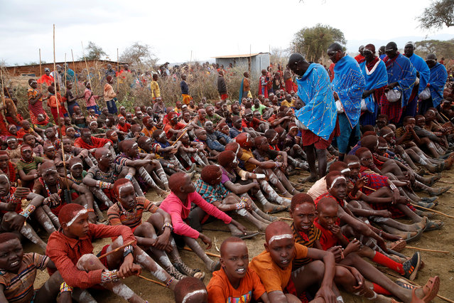 Maasai elders distribute meat to children, taking part in an initiation into an age group ceremony near the town of Bisil, Kajiado county, Kenya on August 23, 2018. (Photo by Baz Ratner/Reuters)