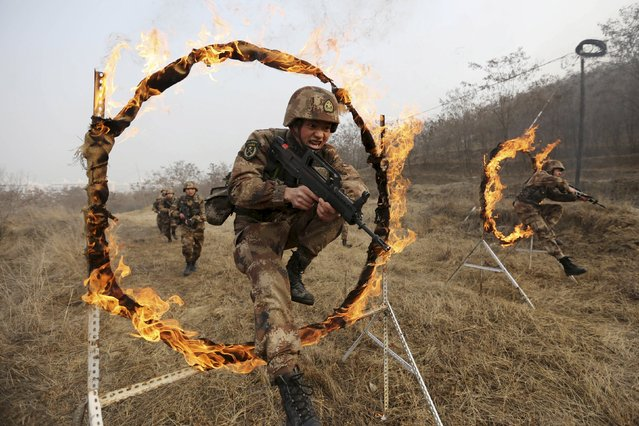 Soldiers of People's Liberation Army (PLA) Lanzhou Military Region jump through a burning obstacle during a training session at a military base in Tianshui, Gansu province, China, January 6, 2016. (Photo by Reuters/Stringer)