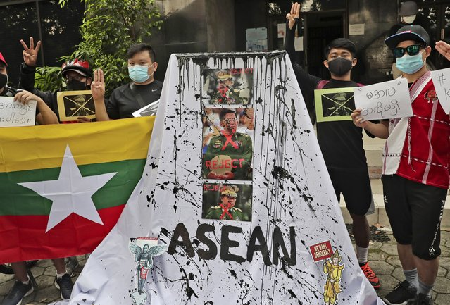 Activists display posters and defaced portraits of Myanmar's Commander-in-Chief Senior General Min Aung Hlaing during a rally against the military coup in Jakarta, Indonesia, Saturday, April 24, 2021. Southeast Asian leaders met Myanmar's top general and coup leader in an emergency summit in Indonesia Saturday, and are expected to press calls for an end to violence by security forces that has left hundreds of protesters dead as well as the release of Aung San Suu Kyi and other political detainees. (Photo by Tatan Syuflana/AP Photo)