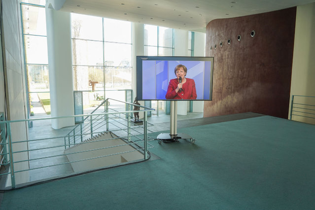 """German Chancellor Angela Merkel is displayed on a screen as she attends the digital dialogue series """"in conversation with the German Chancellor"""" at the Chancellery in Berlin, Germany, on April 27, 2021. (Photo by Carstensen Jörg/Pool via AFP Photo)"""