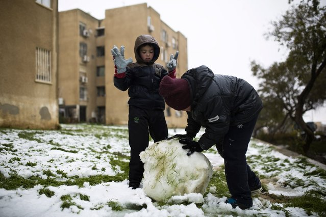 Youths make a snowball in the southern Israeli city of Arad February 20, 2015. (Photo by Amir Cohen/Reuters)