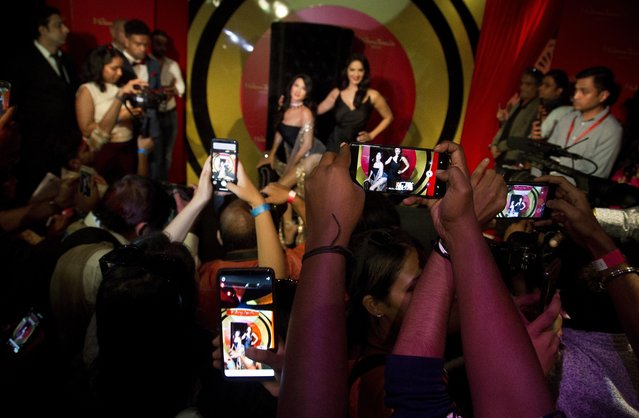 People raise their mobile phones to take photos and videos of Bollywood actress and former p*rn star Sunny Leone during the unveiling of her wax likeness at the Madame Tussauds museum in New Delhi, India, Tuesday, September 18, 2018. (Photo by Anupam Nath/AP Photo)