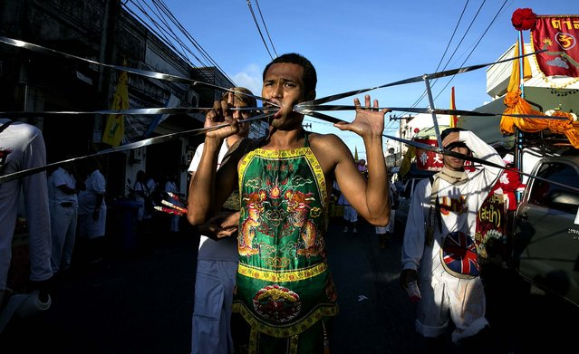 Vegetarian Festival devotees parade through the streets of Phuket. (Photo by Paula Bronstein/Getty Images)
