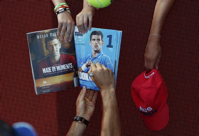 Serbia's Novak Djokovic signs autographs after winning his first round match against South Korea's Hyeon Chung at the Australian Open tennis tournament at Melbourne Park, Australia, January 18, 2016. (Photo by Jason O'Brien/Reuters)