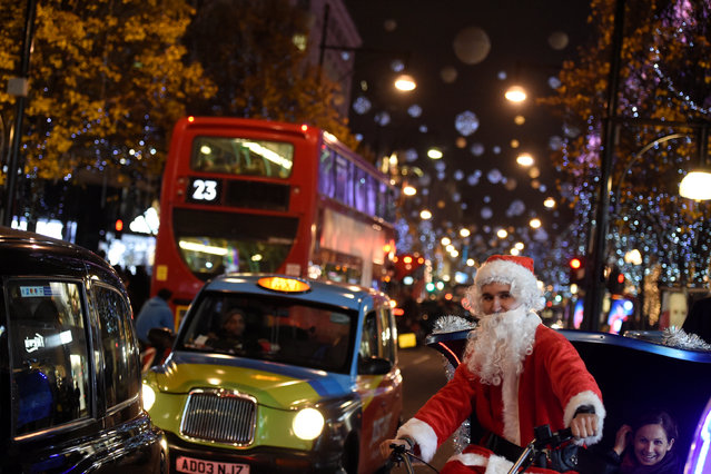 A man dressed as Santa Claus cycles on Oxford Street, which is illuminated with Christmas lights, in  London, Britain, December 9, 2016. (Photo by Clodagh Kilcoyne/Reuters)