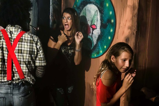 Fright Nights attendees make a turn through one of four haunted houses at this year's spooking season setup at the South Florida Fairgrounds. This house is named The Smiths and was created by Craig McInnis. (Photo by The Palm Beach Post)