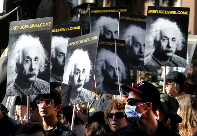 "Protestors hold up banners depicting theoretical physicist Albert Einstein with the hashtag ""#refugeeswelcome"" as they join over a thousand demonstrators marching on International Migrants Day through downtown Los Angeles, California, USA, 18 December 2016. Many of the demonstrators protested the election of Donald Trump and called on the Electoral College to change their ballots to reflect the will of the people where Democratic Presidential candidate Hillary Clinton won almost three million more votes than her Republican rival. (Photo by Mike Nelson/EPA)"