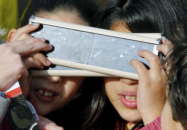 Children react as they wear protective glasses to watch a partial solar eclipse in a square of Pontevedra in the northwest Spain March 20, 2015. (Photo by Miguel Vidal/Reuters)