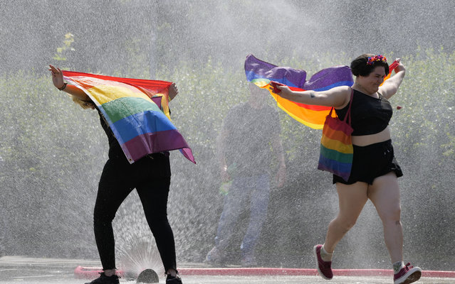 A women with a rainbow flag cools off in a sprinkler ahead of the Equality Parade, the largest LGBT pride parade in Central and Eastern Europe, in Warsaw, Poland, Saturday, June 19, 2021. (Photo by Czarek Sokolowski/AP Photo)