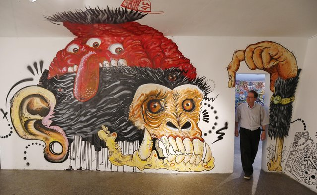 In this March 12, 2015 photo, a man tours a graffiti exhibition at the Museum of Modern Art, in Bogota, Colombia. The city-run museum recently held an exhibition highlighting the work of Bogota street artists who go by aliases such as Joems and the MonsTruacioN collective. (Photo by Fernando Vergara/AP Photo)