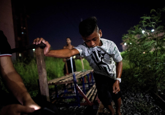 """This photo taken on October 19, 2018 shows a """"trolley boy"""" pushing a home- made cart with passengers on a train track in Manila, Philippines. (Photo by Noel Celis/AFP Photo)"""