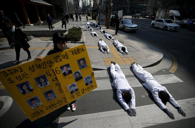 "A woman holds a banner bearing portraits of victims of sunken ferry Sewol next to Buddhist believers performing during a ""three steps one bow"" ceremony to urge the government to salvage the sunken ferry Sewol as soon as possible, in central Seoul March 26, 2015. (Photo by Kim Hong-Ji/Reuters)"