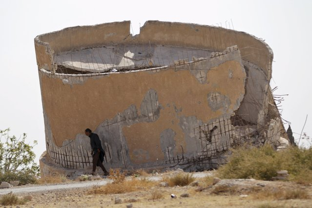 A man walks past a damaged water tank in Deir Sharqi village in Idlib Governorate, Syria October 19, 2015. (Photo by Khalil Ashawi/Reuters)