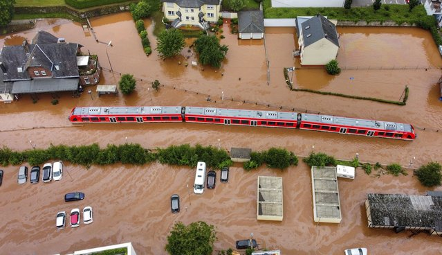 A regional train sits in the flood waters at the local station in Kordel, Germany, Thursday July 15, 2021 after it was flooded by the high waters of the Kyll river. (Photo by Sebastian Schmitt/dpa via AP Photo)