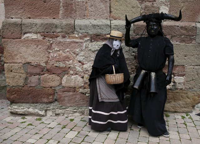 """A reveller (R), dressed as """"Diablos de Luzon"""" (Luzon Devils), stands next to a person dressed as a """"Mascaritas"""" during carnival celebrations in the village of Luzon, Spain, February 6, 2016. (Photo by Sergio Perez/Reuters)"""