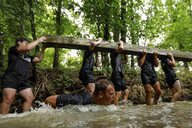 """Heritage high school football player Dylan Hodges falls into a creek while he and his teammates lift a log during a voluntary faith based leadership training camp put on by the organization """"I AM 4"""" in Ringgold, Ga., on Monday, July 12, 2021. The camp, which was lead by Air Force veteran IV Marsh and Army veteran Dan Durbin, who are both pastors, was meant to push the players who volunteered physically, mentally, and spiritually. (Photo by Troy Stolt/Chattanooga Times Free Press via AP Photo)"""