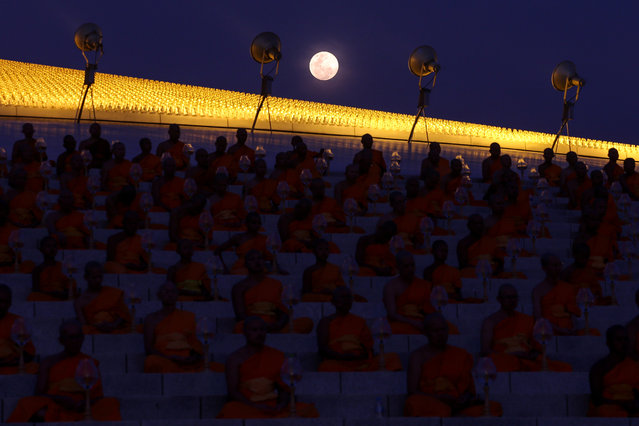 The full moon is seen as buddhist monks attend a ceremony on Makha Bucha Day at Wat Phra Dhammakaya in Pathum Thani, Thailand, March 1, 2018. (Photo by Athit Perawongmetha/Reuters)