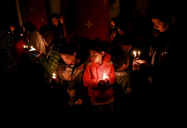 Worshippers holding candles attend an Easter mass on the eve of Easter, at a Catholic church in Shenyang, Liaoning province, April 4, 2015. (Photo by Reuters/Stringer)