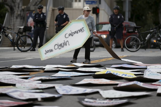 A woman lays cardboard coffins in the middle of the raod during a march to commemorate the more than 617 people they say have been killed by law enforcement in LA County since 2000, in Los Angeles, California April 7, 2015. (Photo by Lucy Nicholson/Reuters)