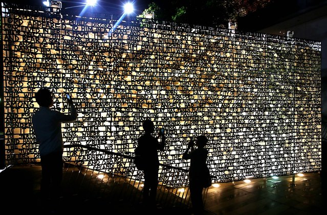 Tourists capture the wall that explains the story of the nativity of Jesus at Christmas Square in Melbourne, Australia. (Photo by Michael Dodge/Getty Images)