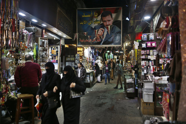 """A poster of the Syrian President Bashar Assad with Arabic reads, """"Assad we are with you for ever"""" hangs up at the popular Hamidiyeh old market in Damascus, Syria, Sunday, February 21, 2016. (Photo by Hassan Ammar/AP Photo)"""