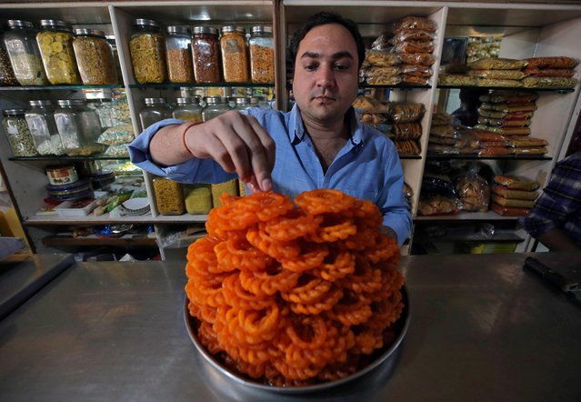 """A man arranges """"Imarti"""", a deep-fried sweet made from flour and then soaked in sugar syrup, at a confectionery shop in Mumbai, January 25, 2019. (Photo by Francis Mascarenhas/Reuters)"""