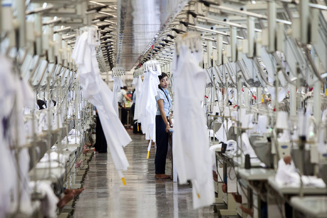A worker stands between rows of sewing machines in the garment area at a PT Sri Rejeki Isman (Sritex) factory in Sukoharjo, Java, Indonesia, on Wednesday, March 27, 2013. (Photo by Dadang Tri/Bloomberg)