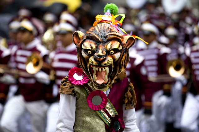 A performer wearing a tiger mask takes part in the New Year's Day Parade in central London on January 1, 2014. (Photo by Justin Tallis/AFP Photo)