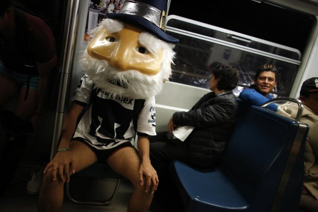 """A man without pants and wearing a mask sits in a subway train during the """"No Pants Subway Ride"""" in Mexico City January 12, 2014. (Photo by Tomas Bravo/Reuters)"""