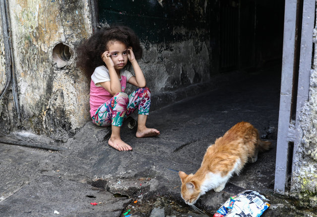 A local girl and a stray cat seen in a street in the San Agustin neighbourhood in Caracas, Venezuela on February 16, 2019. (Photo by Valery Sharifulin/TASS)