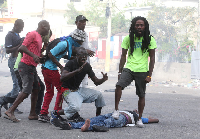 People react next to the dead body of a man during anti-government protests in Port-au-Prince, Haiti, February 12, 2019. (Photo by Jeanty Junior Augustin/Reuters)