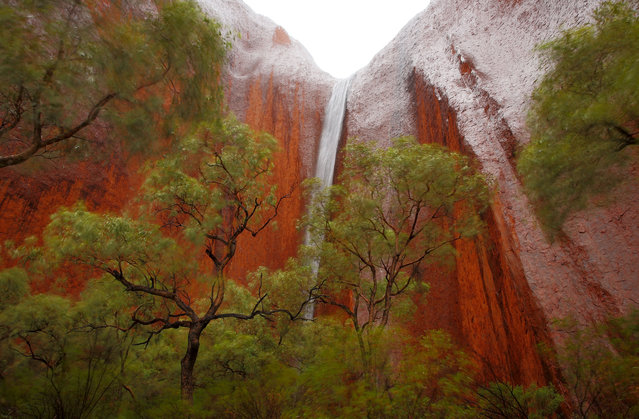 A waterfall is seen in Kantju Gorge as it rains at Uluru on November 27, 2013 in Uluru-Kata Tjuta National Park, Australia. Uluru/ Ayers Rock is a large sandstone formation situated in central Australia approximately 335km from Alice Springs. The site and its surrounding area is scared to the Anangu people, the Indigenous people of this area and is visited by over 250,000 people each year.  (Photo by Mark Kolbe/Getty Images)