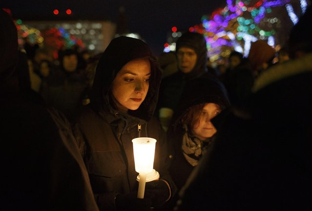 A woman joins others as they gather in remembrance of the victims of Sunday's shooting at a Quebec City mosque, during a vigil in Edmonton, Alberta, Monday, January 30, 2017. A French Canadian known for far-right, nationalist views was charged Monday with six counts of first-degree murder and five counts of attempted murder over the shooting rampage at a Quebec City mosque that Canada's prime minister called an act of terrorism against Muslims. (Photo by Jason Franson/The Canadian Press via AP Photo)