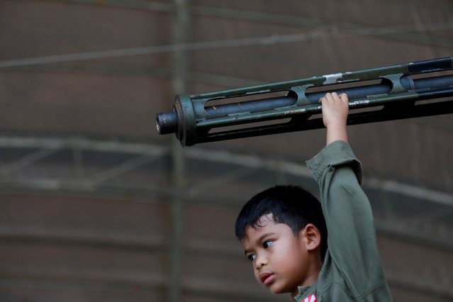 A boy plays with a weapon on the top of an army vehicle during Children's Day celebration at a military facility in Bangkok, Thailand January 12, 2019. (Photo by Soe Zeya Tun/Reuters)