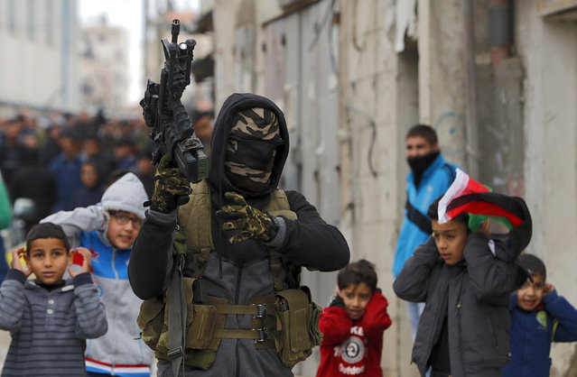 Palestinian militants hold up their automatic machine guns as they fire into the air during the funeral of 23-year-old Palestinian Mohammed Adwan, who was killed during a clash with Israeli forces near Jerusalem overnight, in the Qalandia refugee camp near Ramallah in the West Bank, on April 2, 2019. (Photo by Ahmad Gharabli/AFP Photo)
