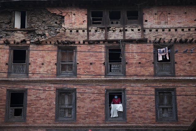 A woman looks from the window of a house that was damaged during the April 25 earthquake in Sakhu, Nepal, Wednesday, May 6, 2015. (Photo by Bernat Amangue/AP Photo)