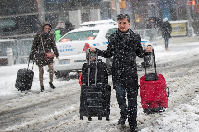 A man carries luggage bags as he crosses the street in Times Square, February 9, 2017 in New York City. (Photo by Drew Angerer/Getty Images)